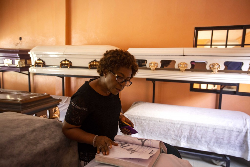 In this March 11, 2020 photo, morgue worker Evala Jeanty checks a list of coffin models chosen by the parents of children who died in a Feb. 13, 2020 ...