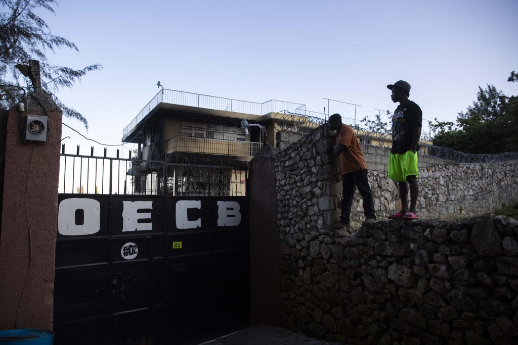 FILE - In this March 14, 2020 file photo, residents stand on top of a wall to see inside the property of a children's home run by the Church of Bible ...