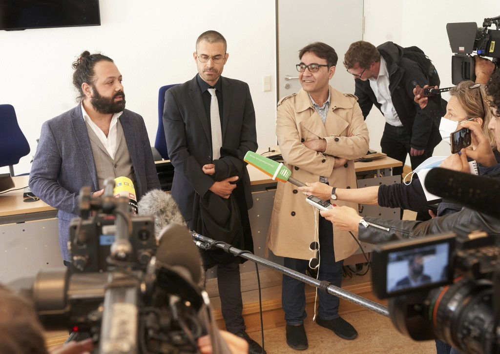 The joint plaintiffs Wassim Mukdad, from left, Patrick Kroker, attorney, and Hussein Ghrer talk to journalists after the first day's trial in Koblenz,...