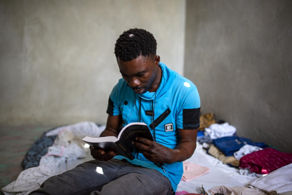 Eustache Arismé reads the Bible inside his room in Tabarre, Haiti, March 12, 2020. Arismé's two daughters Nedjie, 4, and Vanise, 3, died in the Feb. 1...