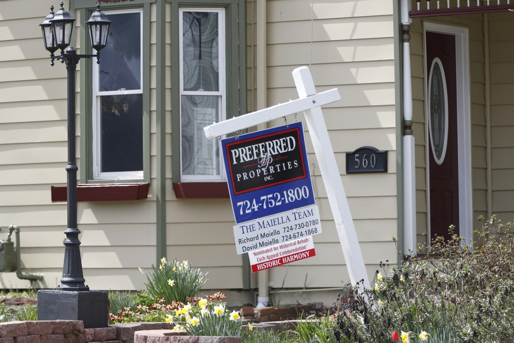 This April 16, 2020 photo shows a real estate company sign that marks a home for sale in Harmony, Pa.  U.S. new home sales plunged 15.4% in March as t...