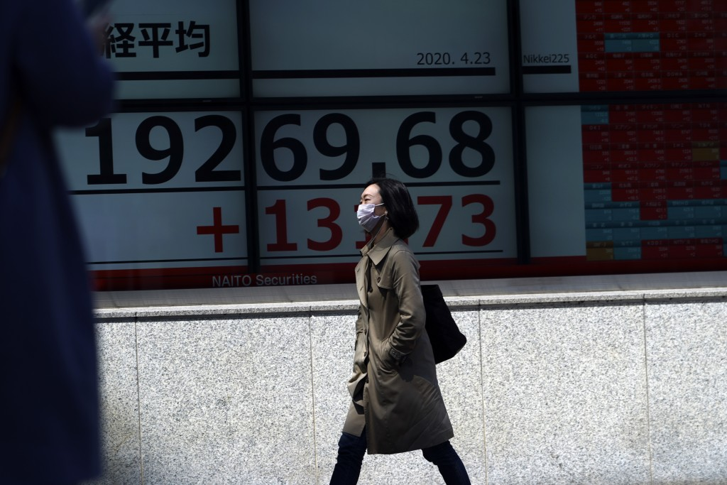 A woman wearing a mask against the spread of the new coronavirus walks past an electronic stock board showing Japan's Nikkei 225 index at a securities...