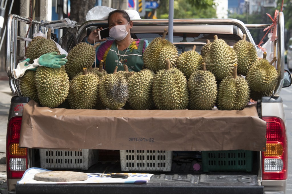 A fruit vendor wearing a face mask to protect from the new coronavirus talks on a mobile phone near durian on her van in Bangkok, Thailand, Thursday, ...