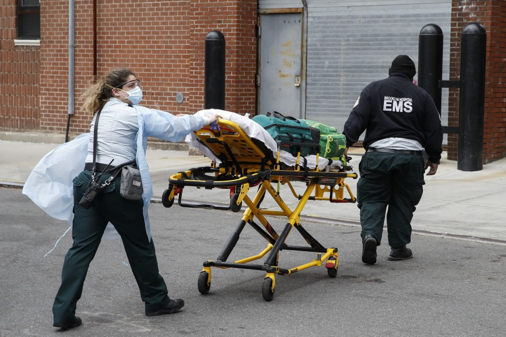 FILE - In this April 17, 2020 file photo, emergency medical workers arrive at Cobble Hill Health Center in the Brooklyn borough of New York for an eme...