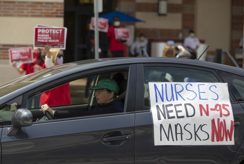 FILE - In this April 13, 2020, file photo, a car passes nurses protesting the lack of N95 respirators and other Personal Protective Equipment outside ...