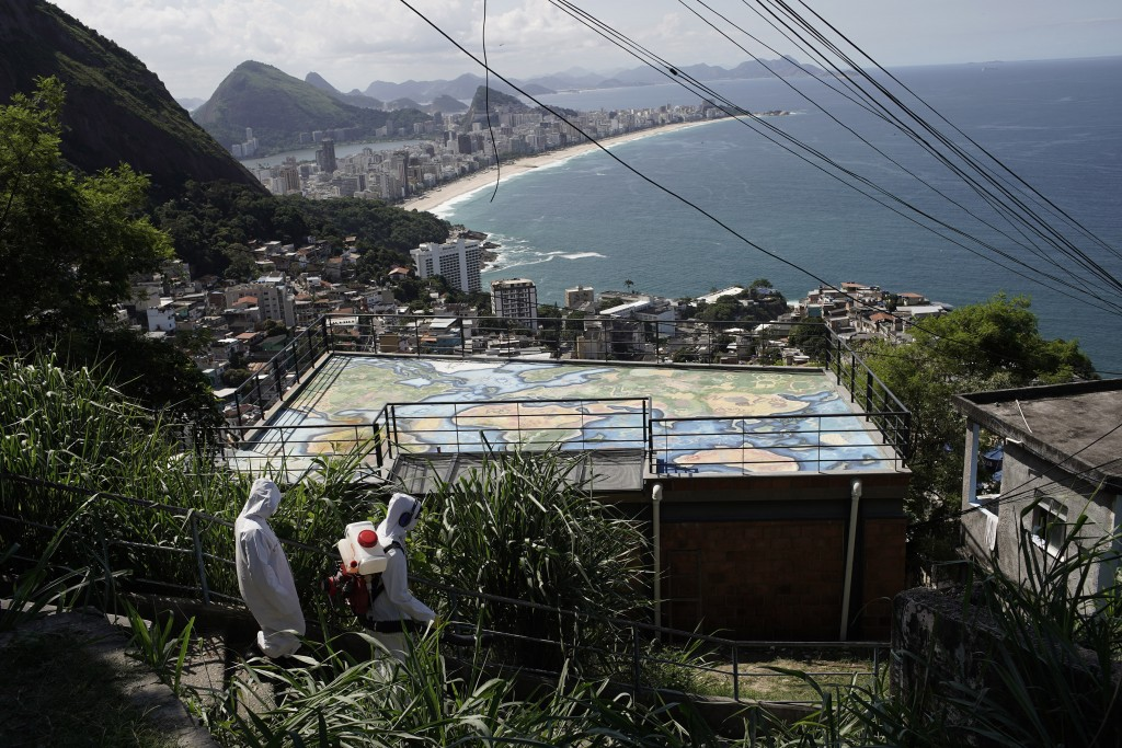Water utility workers from CEDAE disinfect in the Vidigal favela, which overlooks the oceanfront Leblon and Ipanema neighborhoods, in an effort to cur...
