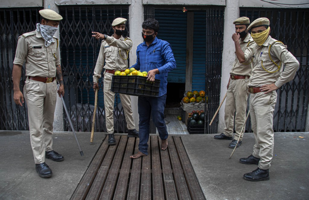 Indian security personnel seize fruits from a vendor who was selling them during nationwide lockdown in Gauhati, India, Thursday, April 23, 2020. As g...