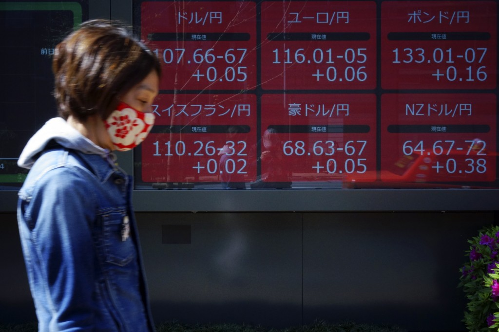 A woman wearing a mask to help stop the spread of the new coronavirus walks past an electronic stock board showing Japan yen and other foreign currenc...