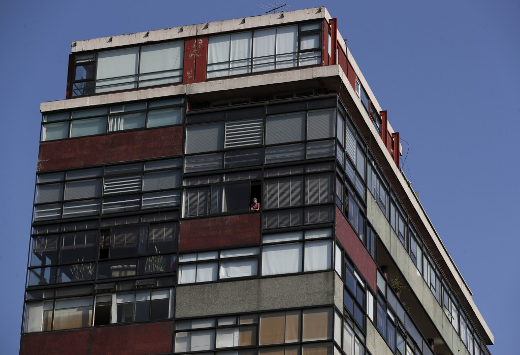 A person peers from the window of an apartment building on Paseo de la Reforma in Mexico City, Thursday, April 23, 2020, as many residents stay home t...