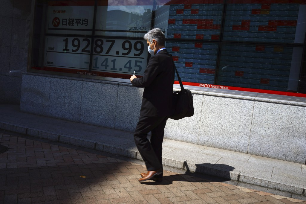 A man wearing a mask to help stop the spread of the new coronavirus walks past an electronic stock board showing Japan's Nikkei 225 index at a securit...
