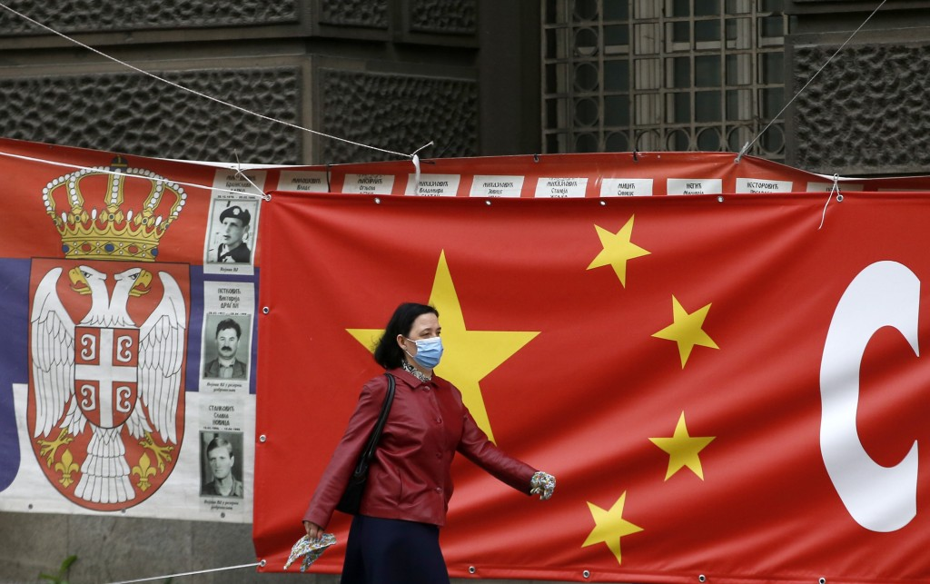 FILE - In this April 13, 2020, file photo, a woman wearing a face mask walks by a Chinese flag placed on a street prior a curfew set up to limit the s...