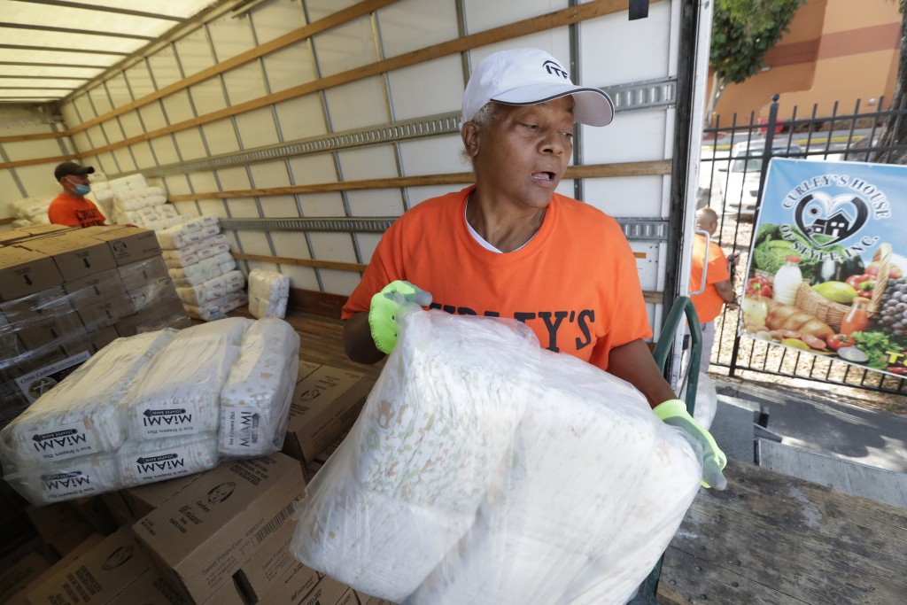 Zelma Strachan, right, and Robert Spicker unload diapers from a truck at Curley's House of Style, Inc., food bank, Thursday, April 23, 2020, in Miami....
