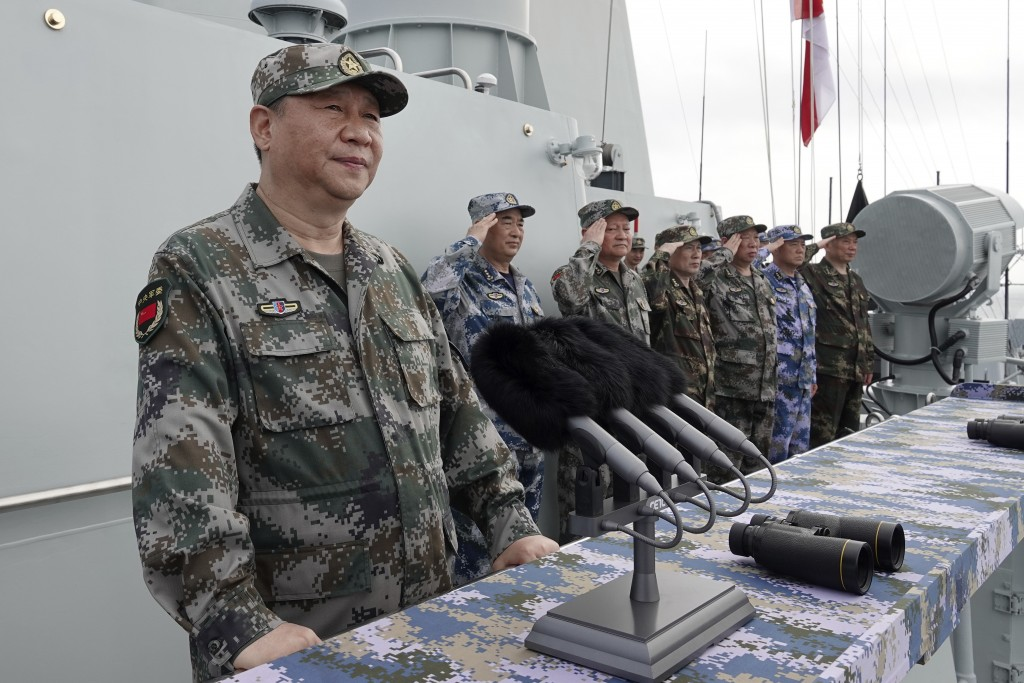 China's leader Xi Jinping reviews troops aboard ship.