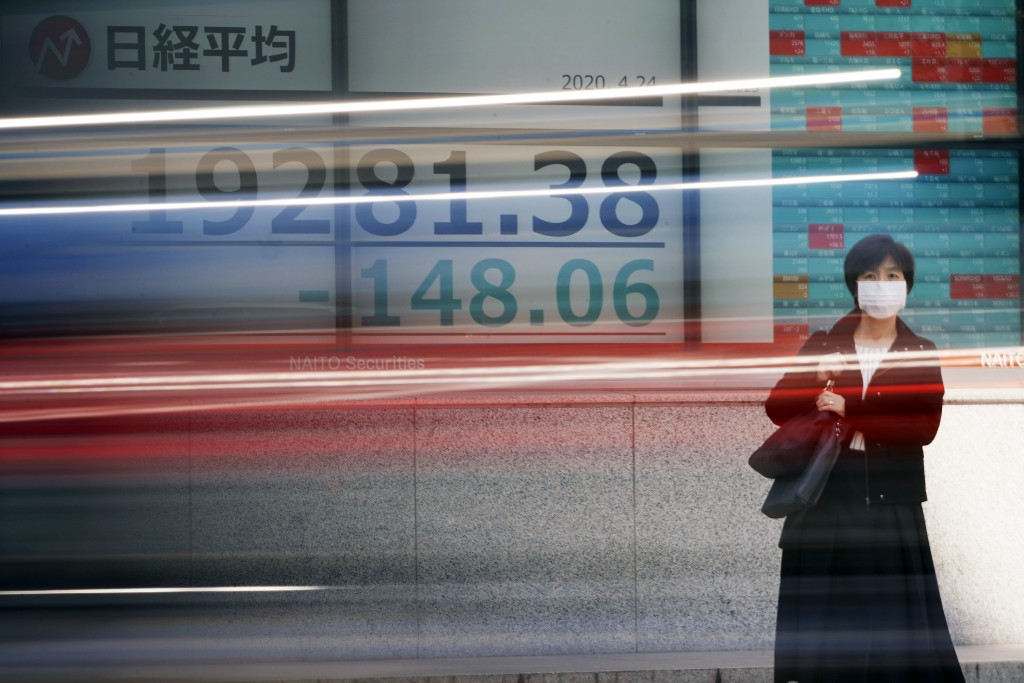 A woman wearing a mask to help stop the spread of the new coronavirus stands near an electronic stock board showing Japan's Nikkei 225 index at a secu...