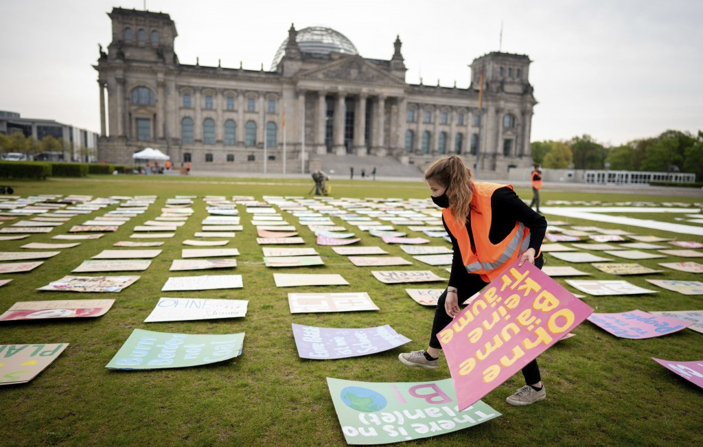 Luisa Neubauer of Fridays for Future movement lays out protest posters for climate protection in front the German parliament building the Reichstag in...