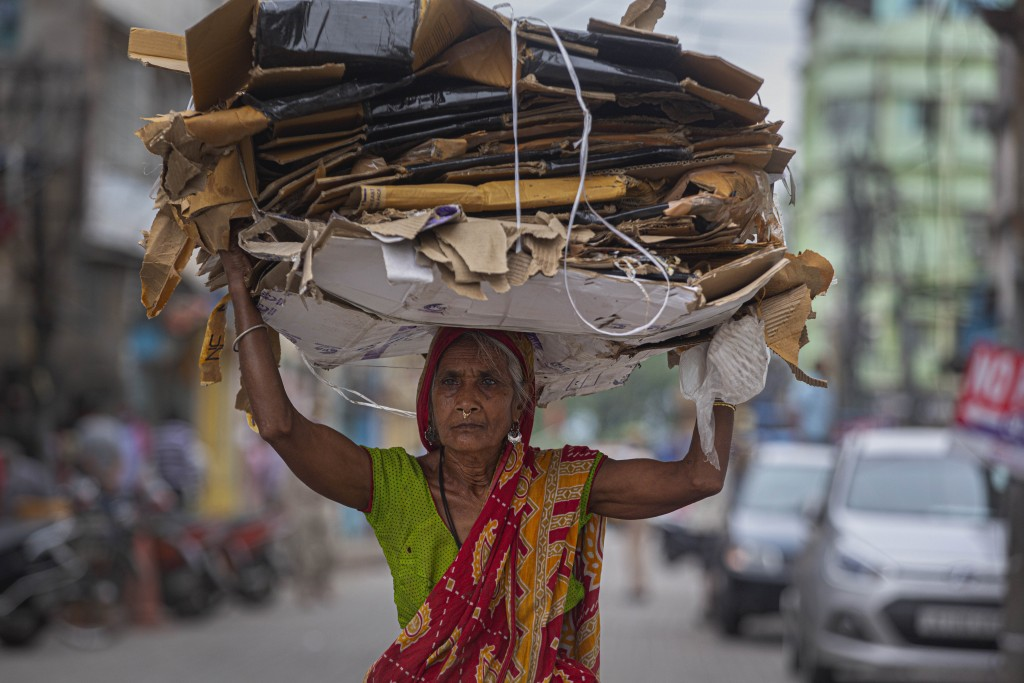 An elderly Indian woman carries recyclable carton boxes on her head during nationwide lockdown in Gauhati, India, Thursday, April 23, 2020. As governm...