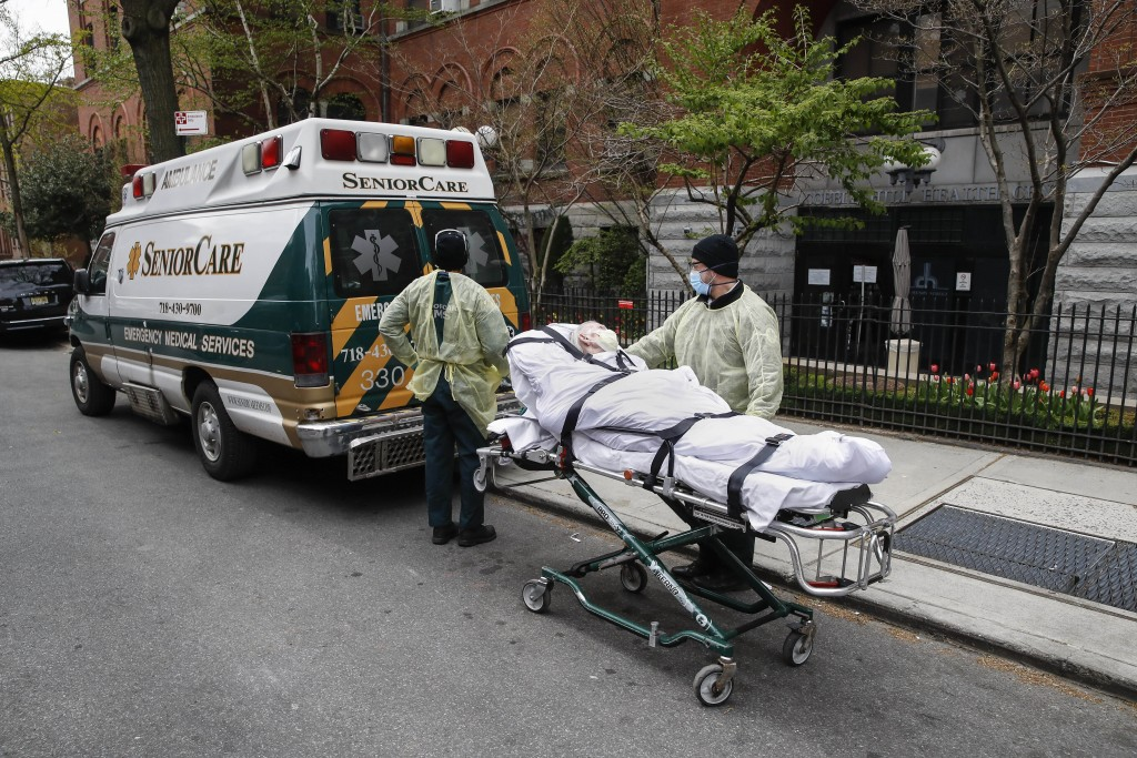 FILE- In this April 17, 2020 file photo, a patient is wheeled out of Cobble Hill Health Center by emergency medical workers in the Brooklyn borough of...