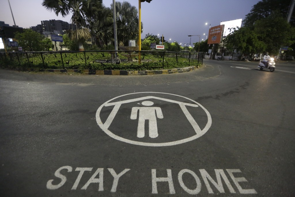 An Indian commuter rides past an awareness message painted on road during lockdown to control the spread of the new coronavirus in Ahmedabad, India, T...