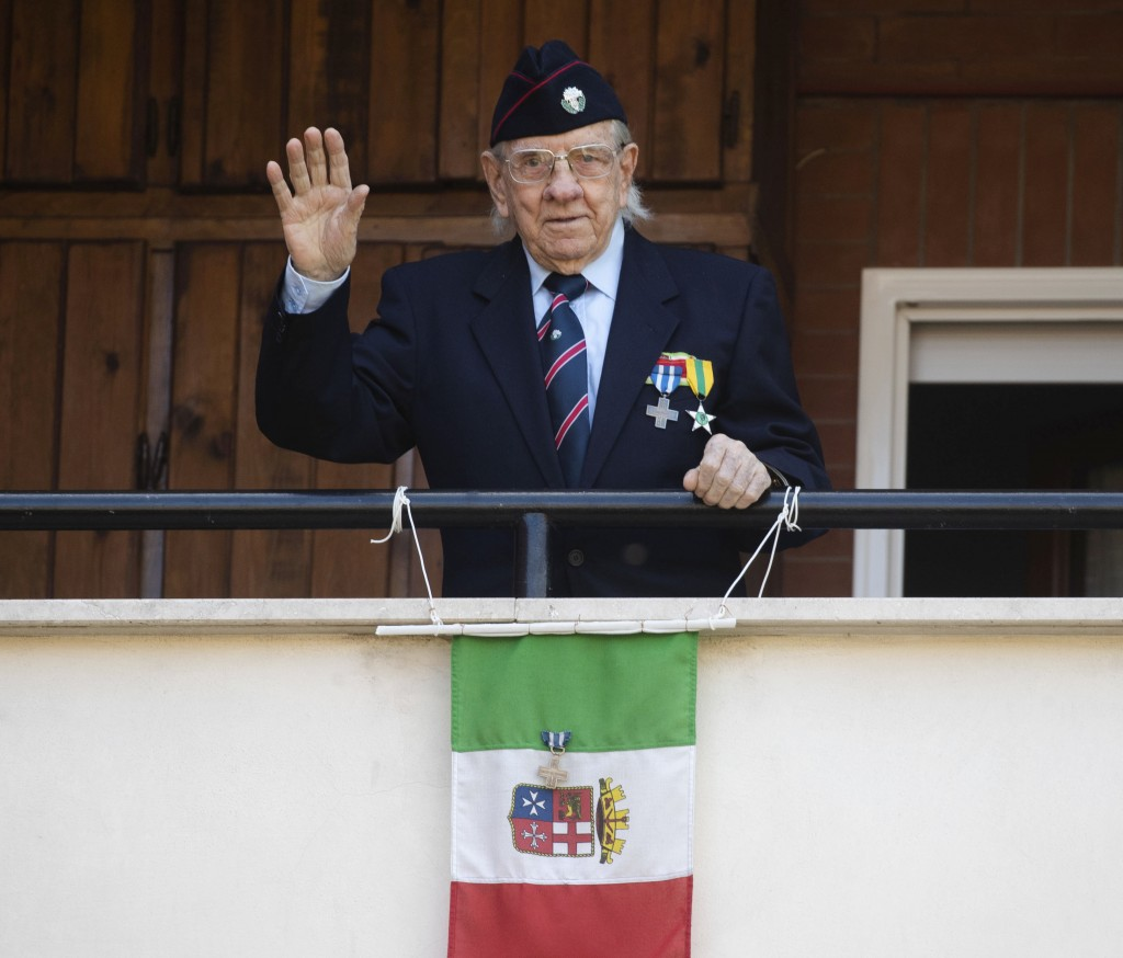 Former partisan Rodolfo Lai, 92, nicknamed Rudy, waves from his balcony in Rome, Thursday, April 23, 2020.  On April 25 every year Italy celebrates th...
