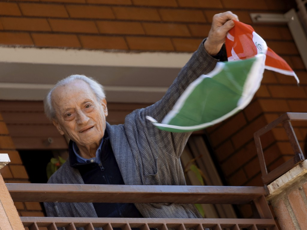Former partisan Modesto Di Veglia, 93, waives his tricolored ANPI (Italian Partisans National Association) scarf from the balcony of his apartment in ...
