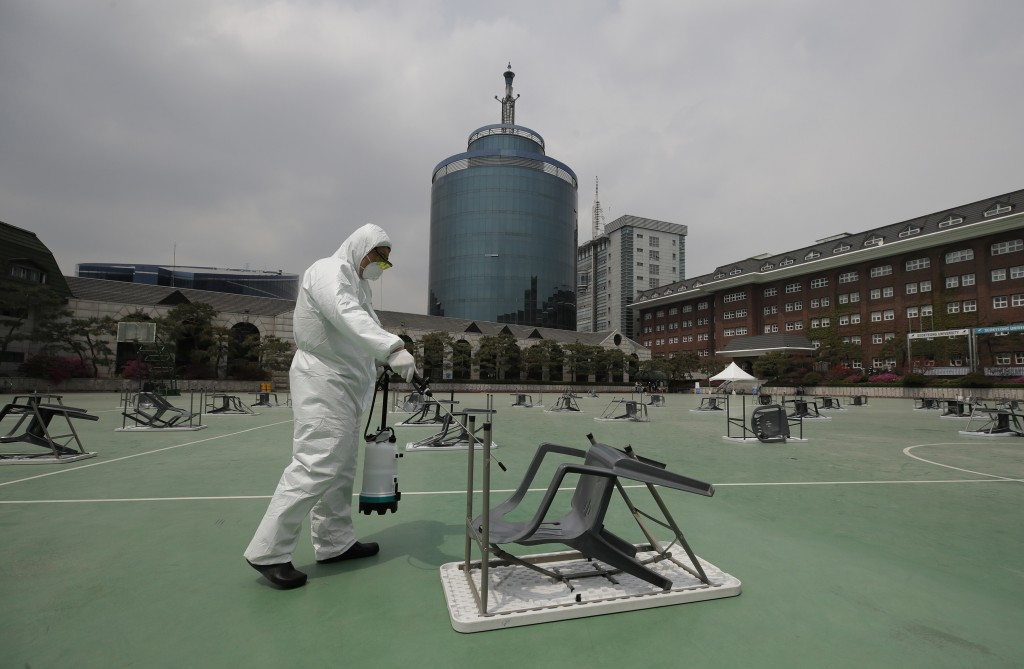 A worker wearing protective gears sprays disinfectant at desks and chairs before an insurance planner qualification exam in Seoul, South Korea, Saturd...