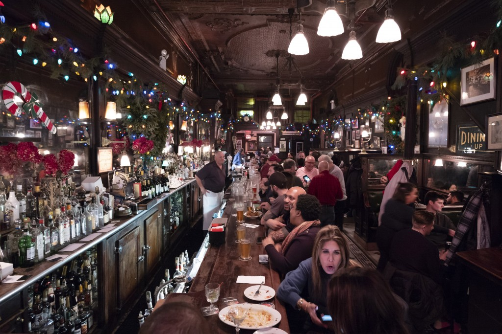 FILE - In this Dec. 27, 2019, file photo, customers mingle in New York's Old Town Bar. With New York City at the epicenter of the coronavirus outbreak...