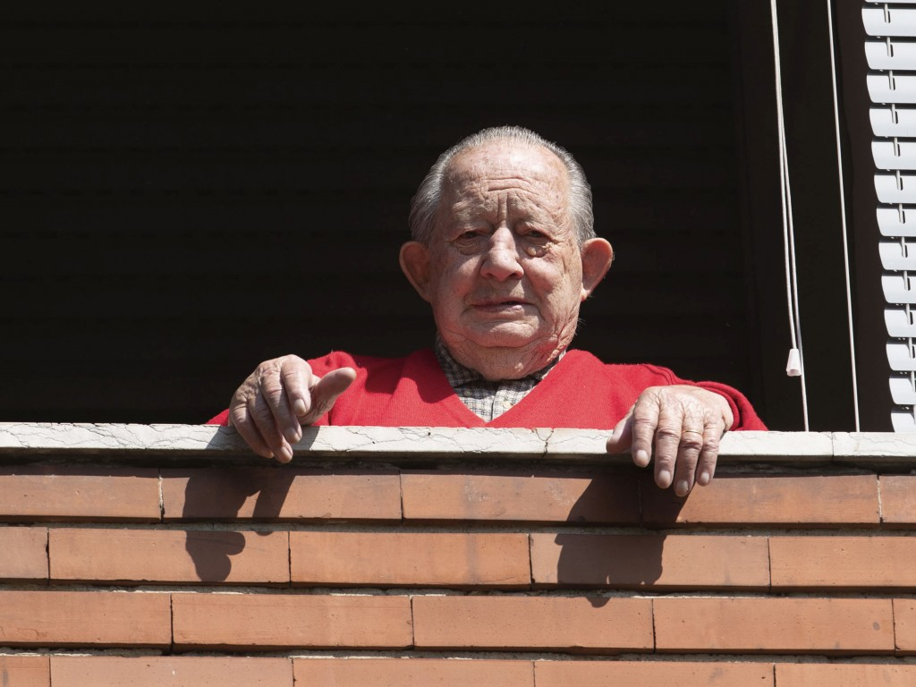 Former partisan Mario Ciurli, 95, nicknamed 'Mariet', poses at his window, in Milan, Italy, Friday, April 24, 2020. On April 25 every year Italy celeb...