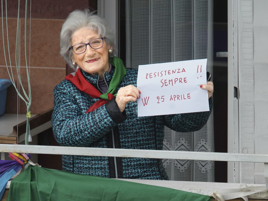 "Former partisan Teresa Vergalli, 93, nicknamed Annuska, holds a note reading in Italian ""Resistance always, long live Aprile 25"", as she poses at her ..."