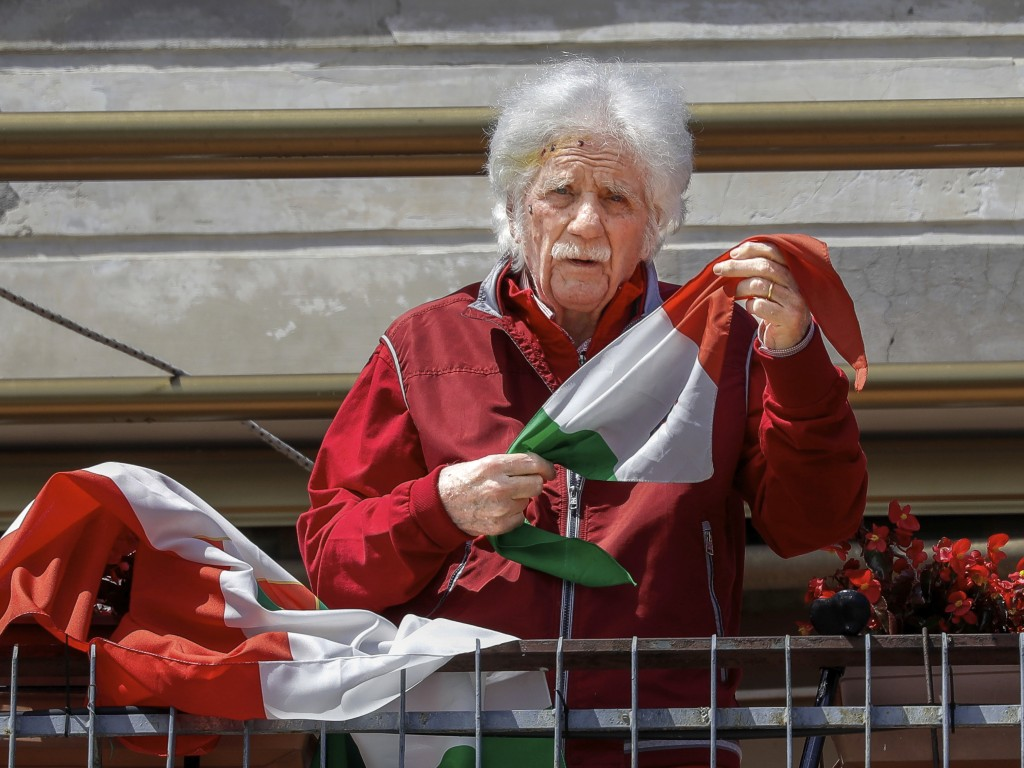 Former Partisan Odino Bernabei, 95, poses with an Italian flag on the terrace of his apartment, in Rome, Thursday, April 23, 2020. Odino Bernabei took...