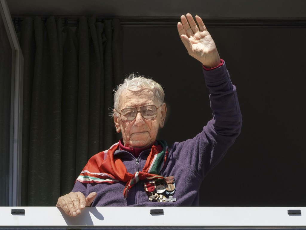 Former partisan Sante Giovannetti, 94, waves from a window of his house, in Rome, Friday, April 24, 2020. On April 25 every year Italy celebrates the ...