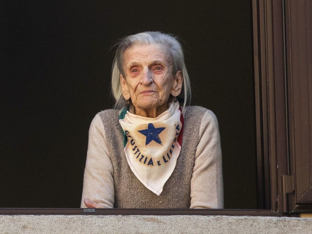 Former partisan Laura Wronowki, 96, poses at her window in Milan, Italy, Friday, April 24, 2020.  On April 25 every year Italy celebrates the end of t...