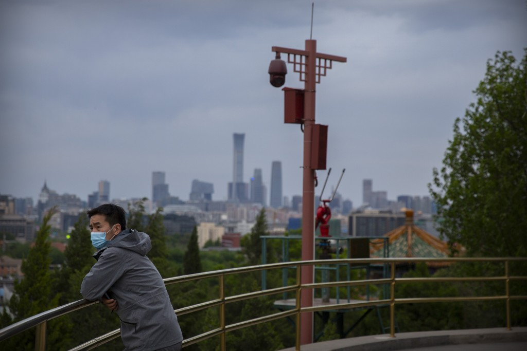 A man wearing a face mask to protect against the spread of the new coronavirus stands on a hilltop at a public park in Beijing, Saturday, April 25, 20...