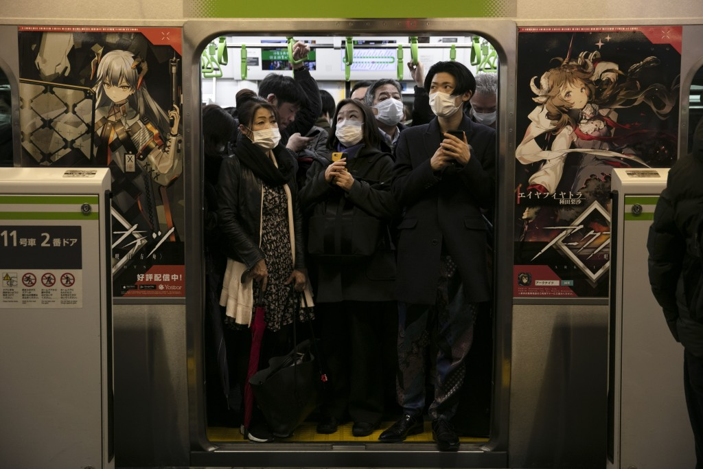 FILE - In this March 2, 2020, file photo, commuters wearing masks stand in a packed train at the Shinagawa Station in Tokyo. When the Japanese governm...