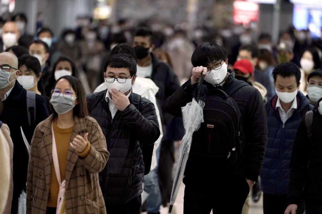 FILE - In this April 20, 2020, file photo, a station passageway is crowded with face mask wearing commuters during a rush hour, in Tokyo. When the Jap...