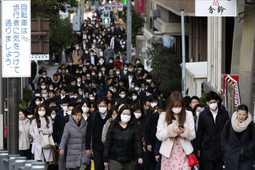 FILE - In this Feb. 20, 2020, file photo, people wear masks as they commute during the morning rush hour, in Chuo district in Tokyo. When the Japanese...
