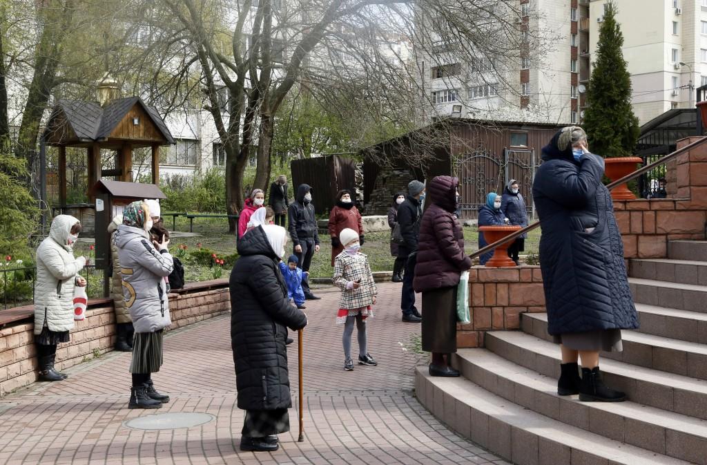 圖為2020年4月烏克蘭民眾在首都基輔一座教堂外,為34年前車諾比核災意外的受害者默哀。(美聯社圖片)