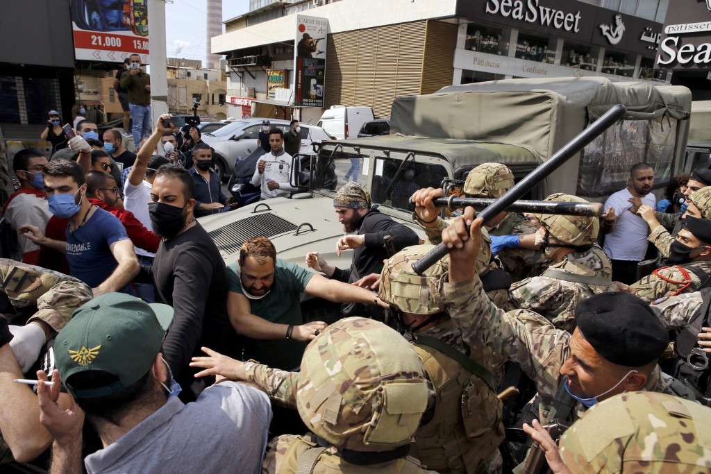Anti-government protesters scuffle with Lebanese army soldiers in the town of Zouk Mosbeh, north of Beirut, Lebanon, Monday, April 27, 2020. Scattered...