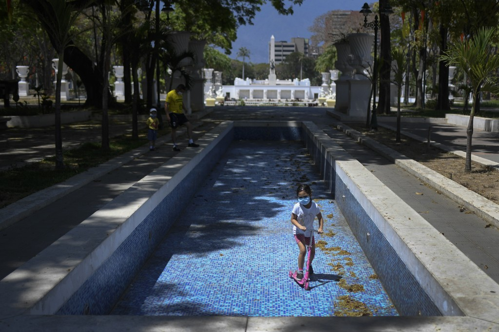 A child wearing a face mask rides her scooter inside an empty water fountain at Los Proceres boulevard in Caracas, Venezuela, Sunday, April 26, 2020. ...