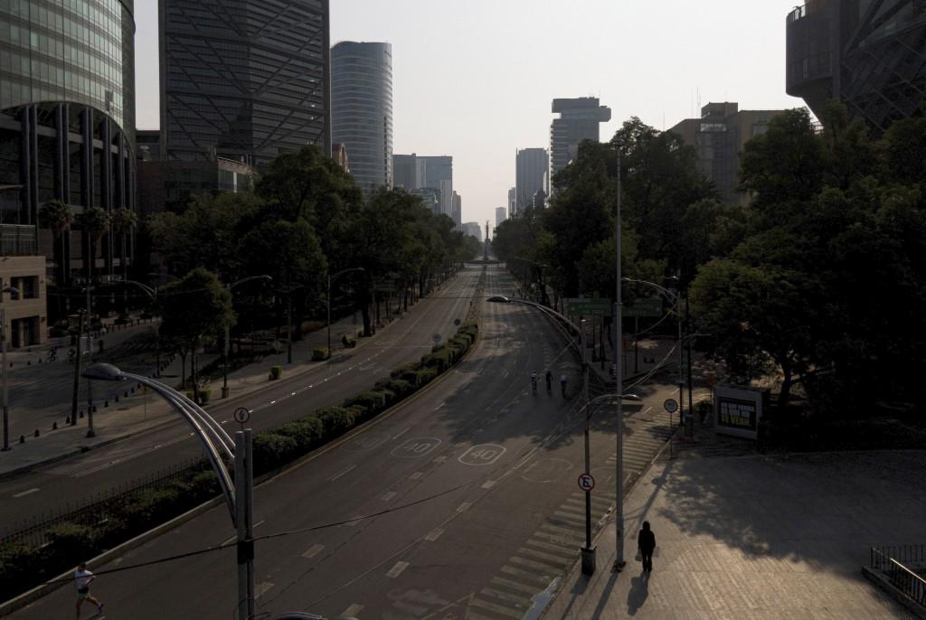 People jog at an empty Paseo de la Reforma in Mexico City, Sunday, April 26, 2020. (AP Photo/Fernando Llano)