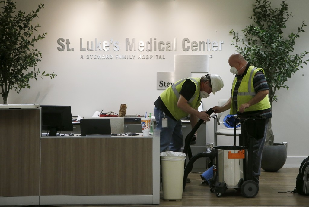 In this April 23, 2020, photo, contract workers join the Army Corps of Engineers as they get the currently dormant St. Luke's Hospital ready for reope...