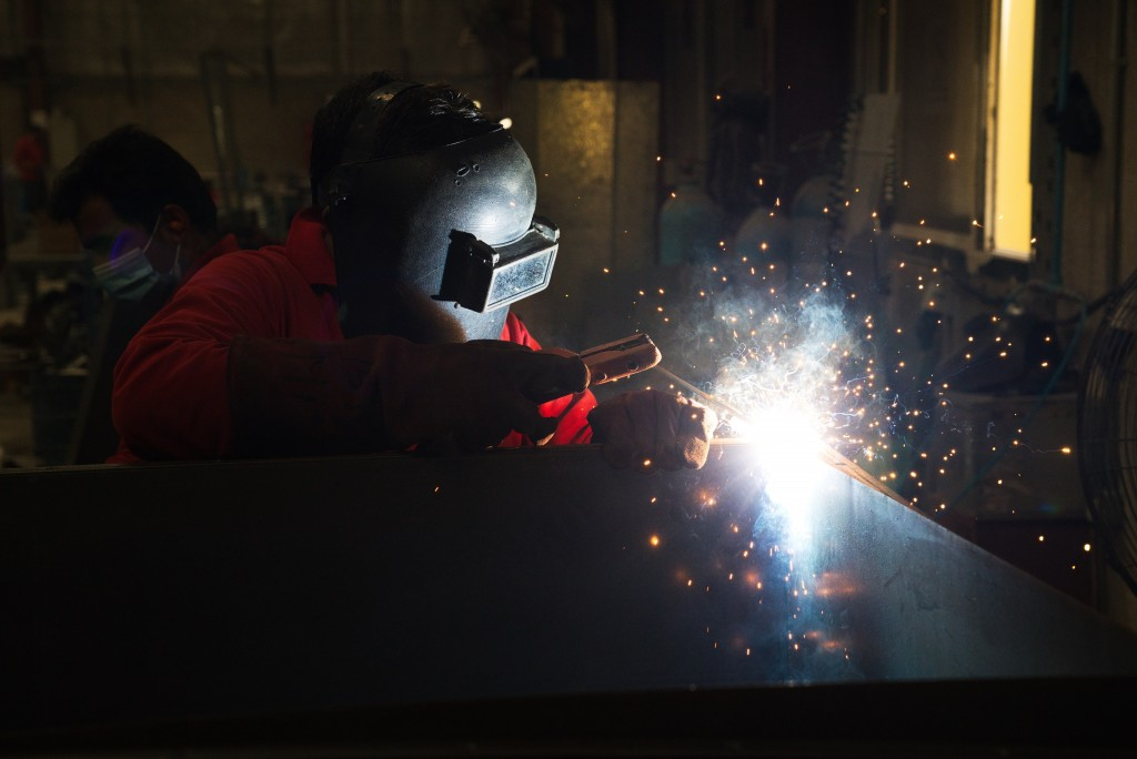 In this Monday, April 27, 2020 photo, a worker welds metal that will be a part of a gate system made by Guard ME that conducts temperature checks and ...