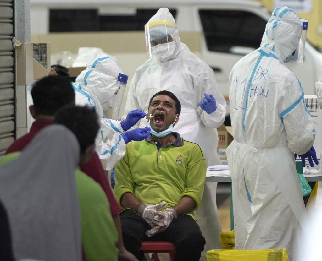 A health worker collects sample for coronavirus testing from a worker at a locked down wet market as one of its traders tested positive for COVID-19 i...