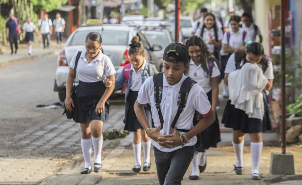 Students arrive to Rigoberto Lopez Perez public school, with very few wearing masks amid the spread of the new coronavirus, at the start of the school...