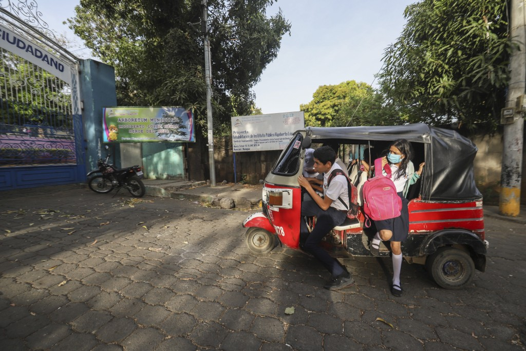 Students arrive in a moto-taxi to Rigoberto Lopez Perez public school, some wearing masks as a precaution amid the spread of the new coronavirus, at t...