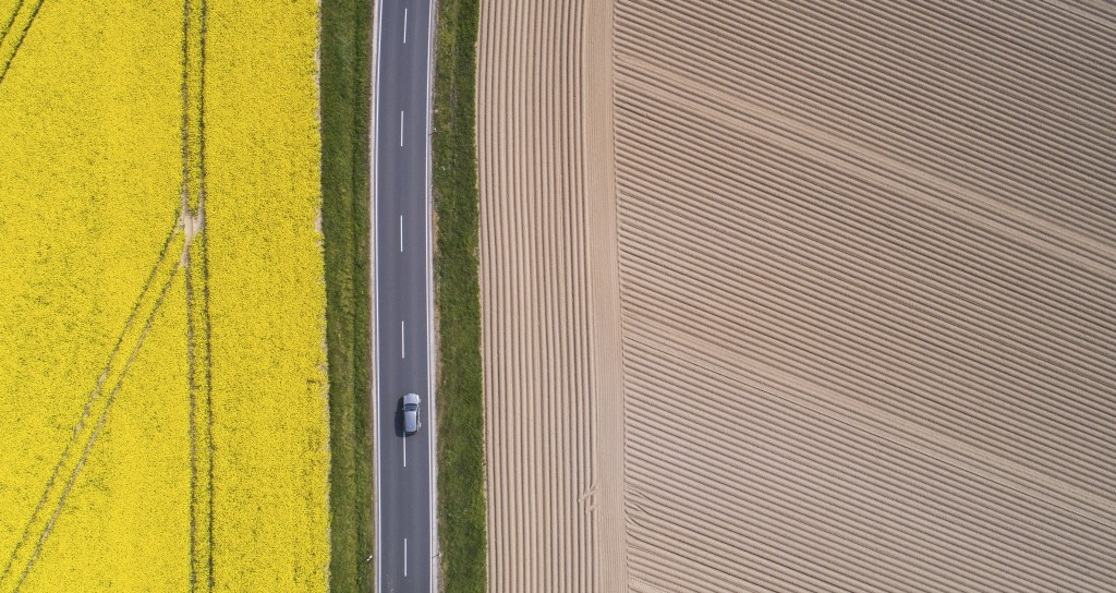 A lorry drives along a country road that between a flowering rape field and a freshly tilled field in Pattensen, Germany, Tuesday, April 28, 2020. (Ju...