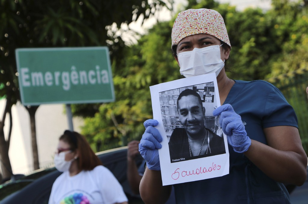 "A health worker holds a photo of a person he said was his colleague who died of COVID-19, at a protest outside ""Pronto Socorro 28 de Agosto"" Hospital ..."