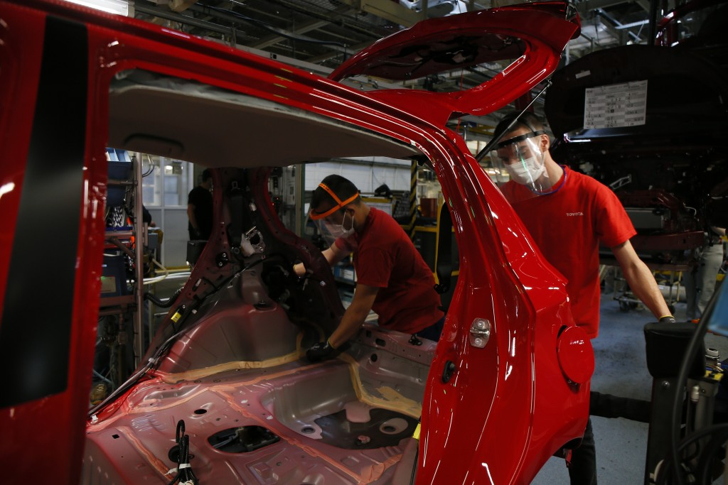 Employees wearing face masks work on a Yaris car at the Toyota car factory in Onnaing, northern France, Tuesday, April 28, 2020. Workers are returning...