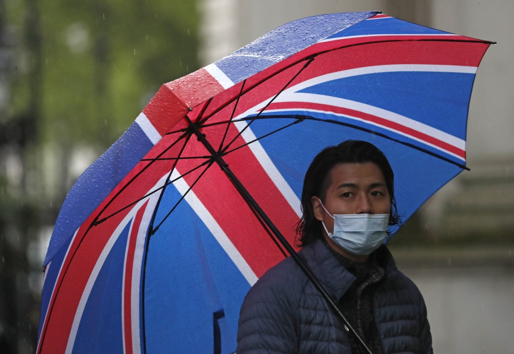 A journalist wearing a face mask to protect against coronavirus shelters under a Union flag umbrella outside 10 Downing Street in London, Tuesday, Apr...