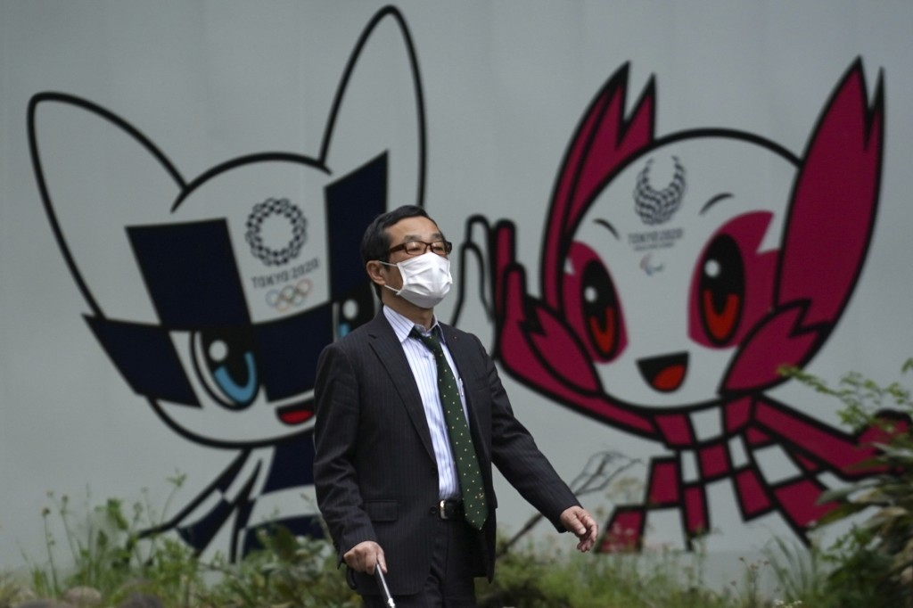 A man with a face mask against the spread of the new coronavirus walks in front of Miraitowa and Someity, mascots for the Tokyo 2020 Olympics and Para...