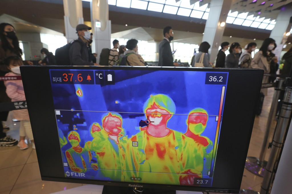 A thermal camera monitor shows the body temperature of passengers as they wait in line before boarding airplanes at the domestic flight terminal of Gi...